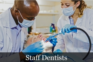 Staff Dentists image showing a dentist and hygenist cleaning a patient's teeth.